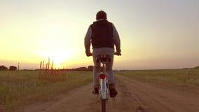 Pojketonåring som rider en cykel Pojketonåringen som rider en cykel, går till naturen längs rörelsen för skottet för banasteadica Arkivbild
