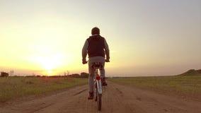 Pojketonåring som rider en cykel Pojketonåringen som rider en cykel, går till naturen längs rörelsen för skottet för banasteadica Royaltyfri Fotografi