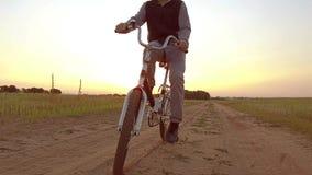 Pojketonåring som rider en cykel Pojketonåringen som rider en cykel, går till naturen längs videoen för rörelse för banasteadicam Royaltyfria Bilder