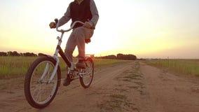 Pojketonåring som rider en cykel Pojketonåringen som rider en cykel, går till naturen längs videoen för rörelse för banasteadicam Arkivfoto