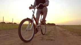 Pojketonåring som rider en cykel Pojketonåringen som rider en cykel, går till naturen längs videoen för rörelse för banasteadicam Royaltyfri Bild