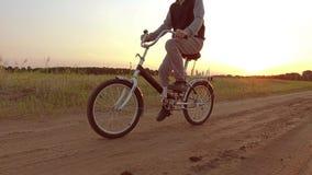 Pojketonåring som rider en cykel Pojketonåringen som rider en cykel, går till naturen längs videoen för rörelse för banasteadicam Royaltyfri Foto
