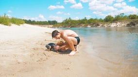 Pojketonåring som slår en våt hund på stranden nära vattnet av en flodultrarapidvideo pojketonåring i sommarbadning stock video