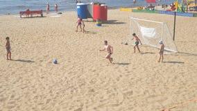Pojketonåringar som spelar fotboll på stranden stock video