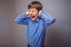 Pojketonåringen skriker räkningar som öron stängde på hans ögon royaltyfri bild