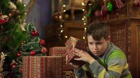 Pojketonåringskakor och kontroller för julklappar Gåvor som staplas under trädet arkivfilmer