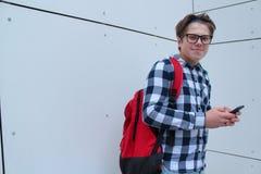 Pojketonåringskolpojke eller student i skjortan som ler med exponeringsglas, röd ryggsäck arkivbilder