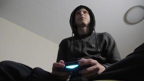 Pojketon?ring i huven som spelar videospel p? konsolen p? gamepaden Den unga ton?riga med huva tr?jan f?r mannen absorberade in arkivfilmer