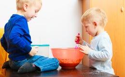 Pojkeungar som bakar kakan. Barn som slår deg med tråd, viftar. Arkivbild