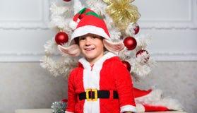 Pojkeunge som kläs som vita konstgjorda öron för gullig varelse för älva magisk och den röda hatten nära julträd Ung ursnygg kvin royaltyfri bild