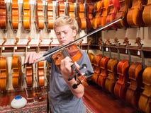 Pojkeviolinist Playing en fiol i en Music Store Fotografering för Bildbyråer
