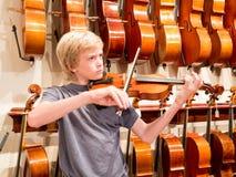 Pojkeviolinist Playing en fiol i en Music Store Arkivbild