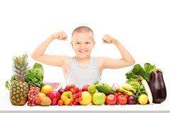 Pojkevisningen tränga sig in bak högen av grönsaker Arkivbild