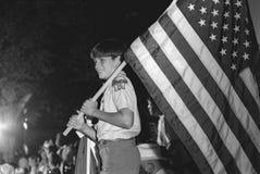 Pojkscouten bär amerikanska flaggan arkivfoto