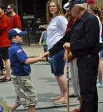 Pojkscouten Shakes Hand av veteran på ståtar Royaltyfria Bilder