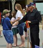 Pojkscouten Shakes Hand av veteran på ståtar Royaltyfri Bild