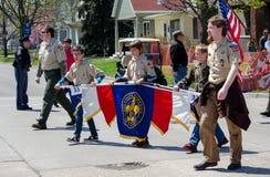 Pojkscouter som marscherar i en ståta royaltyfria foton