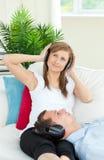 pojkvän henne lyssnande musik till kvinnan Arkivbild