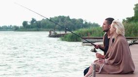 Pojkvän och flickvän som tillsammans fiskar vid floden, kall morgon på sjön, härligt landskap arkivfilmer