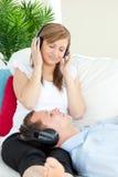 pojkvän som är gullig henne lyssnande musik till kvinnan Royaltyfria Foton