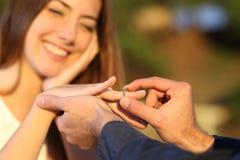 Pojkvän som sätter en förlovningsring i hans flickvänfinger Royaltyfria Foton