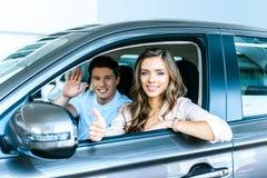 Pojkvän som vinkar en hand, flickvänvisningtumme upp sammanträde i en ny bil i visningslokal arkivfoto