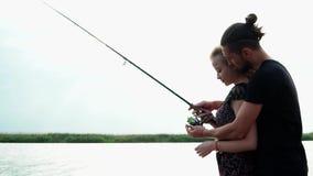 Pojkvännen undervisar hans flickvän att fiska på snurr vid lakesiden, man att krama hans älskvärda kvinna stock video