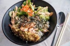 Poké bunke med flambélaxen, Tempuraräka, guacamole, den Masago kaviaren, sallad och sesam på ris och den svarta porslinplattan arkivfoto