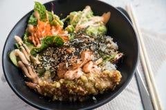 Pokékom met flambézalm, Tempura-garnalen, guacamole, Masago-kaviaar, salade en sesam op rijst en zwarte porseleinplaat stock afbeelding