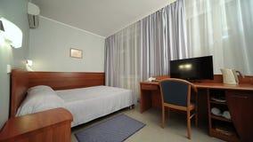 Pokój hotelowy z bliźniaczym łóżkiem, tv, stół Okno światło zdjęcie wideo