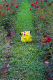 Pokémon center plush doll Pikachu. On public park on the grass between roses Royalty Free Stock Photo