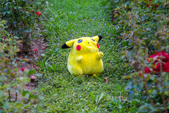 Pokémon center plush doll Pikachu. On public park on the grass between roses Royalty Free Stock Image