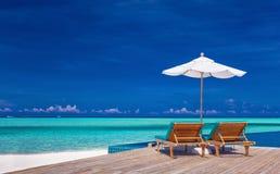 Pokładów krzesła przegapia nieskończoności laguny i basenu z parasolem Obraz Stock