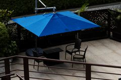 Pok?ad w drewnie z plenerowymi basen?w sto?ami z b??kitn? parasola minimalisty budow? obrazy stock