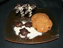 Pokaz Czekoladowi żółwie i drzewka palmowe na cukierze wyrzucać na brzeg z asortowanymi ciastkami na szklanym talerzu czarnym tle fotografia stock