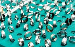 Pokaz z różnymi projektami handmade srebro dzwoni na zieleni Zdjęcie Stock