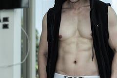 Pokazuje mięśnia ciała przystojny mężczyzna w czarnym sportswear Zdjęcie Royalty Free