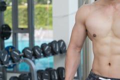 Pokazuje mięśnia ciała przystojny mężczyzna w sprawności fizycznej centrum lub gym, Obrazy Stock