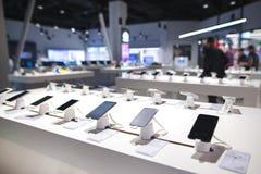 Pokazuje z smartphones w nowożytnym elektronika sklepie Wiele smartphones na półce technologia sklep obraz stock