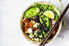 Poke bowl with avocado, black rice, smoked tofu, beans, vegetables, sprouts, white background