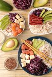 Poke bowl Hawaiian food. a plate of rice, salmon, avocado, cabbage and cheese. next to sesame and fresh avocado on a natural woode royalty free stock photos