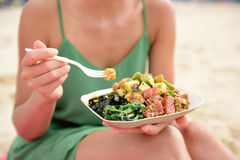 Poke bowl salad plate - a local Hawaii food dish. Poke bowl salad plate. A traditional local Hawaii food dish with raw marinated ahi yellowfin tuna fish. Woman Stock Photo