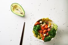 poke bowl with salmon, avocado, cucumber, arugula, broccoli, rice, carrot and sweet onions with chuka salad, with chopsticks and royalty free stock image
