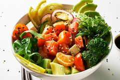 poke bowl with salmon, avocado, cucumber, arugula, broccoli, rice, carrot and sweet onions with chuka salad, chopsticks royalty free stock image
