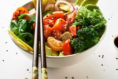 poke bowl with salmon, avocado, cucumber, arugula, broccoli, rice, carrot and sweet onions with chuka salad, chopsticks on a plate stock images