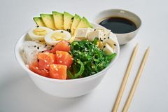 poke bowl with salmon, avocado, rice, Chuka Salad, sweet onions, quail eggs sprinkled with white and black sesame with chopsticks royalty free stock image