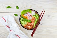Poke bowl with salmon, rice, radish, carrot, cucumber. Hawaiian ahi, a diet meal with fish.