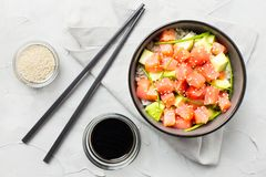 Poke with raw salmon and avocado decorated with green onions and sesame seeds in bowl with soy sauce and chopsticks. stock images