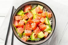 Poke with red fish and avocado decorated with green onions and sesame seeds in bowl with chopsticks. royalty free stock photography