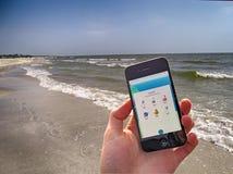 Pokemon去在手扶的智能手机的比赛在海滩夏天背景 图库摄影